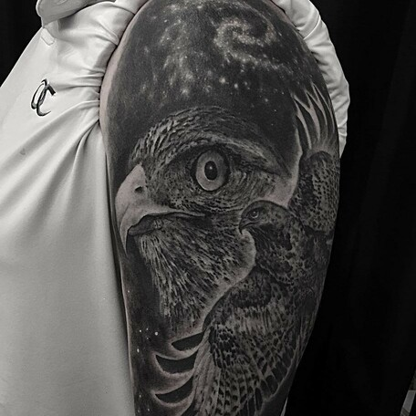 fbc1ecdba932d Bicep tattoo of birds of prey surrounded by a galaxy. Black and grey tattoo  created